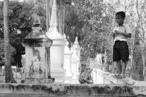 Jeune lao testant son équilibre sur le mur d'enceinte d'un temple